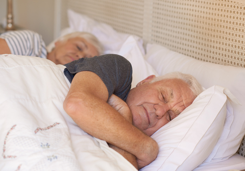 Senior man sleeping soundly while lying in bed in the morning with his wife asleep behind him