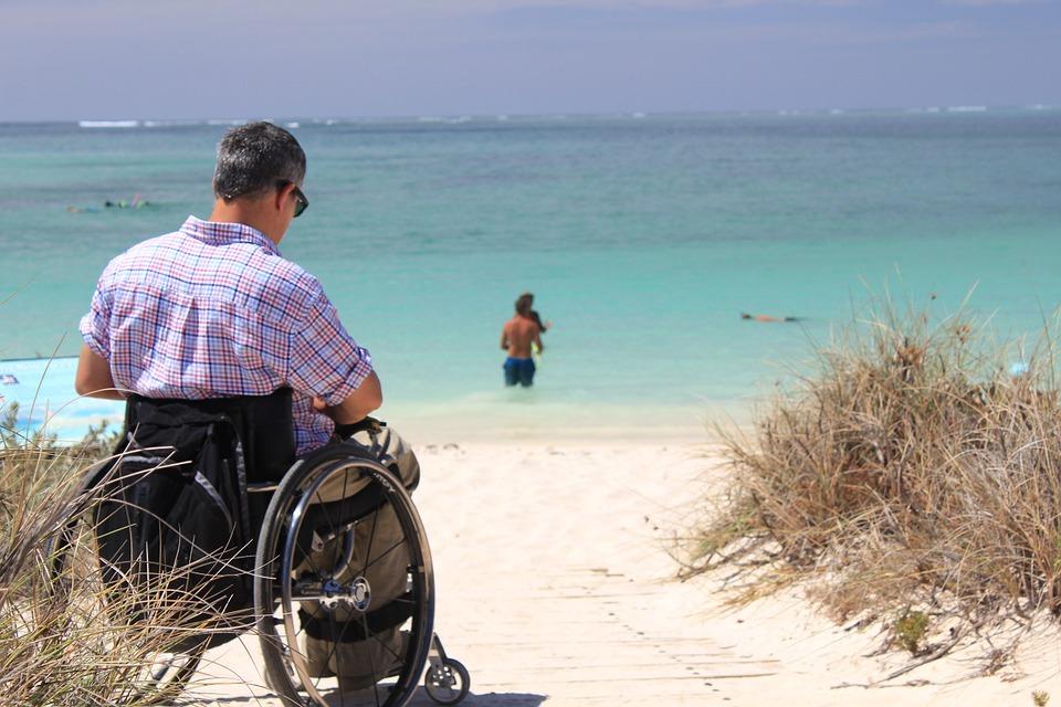 A man in a wheelchair on the beach.