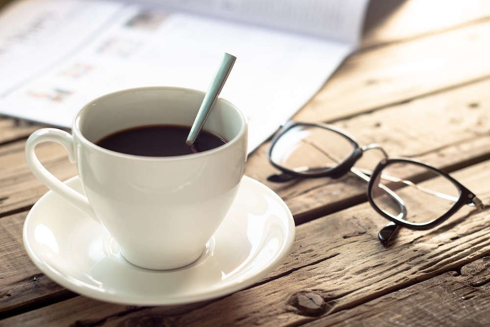 Cup of coffee and reading glasses on wooden table.