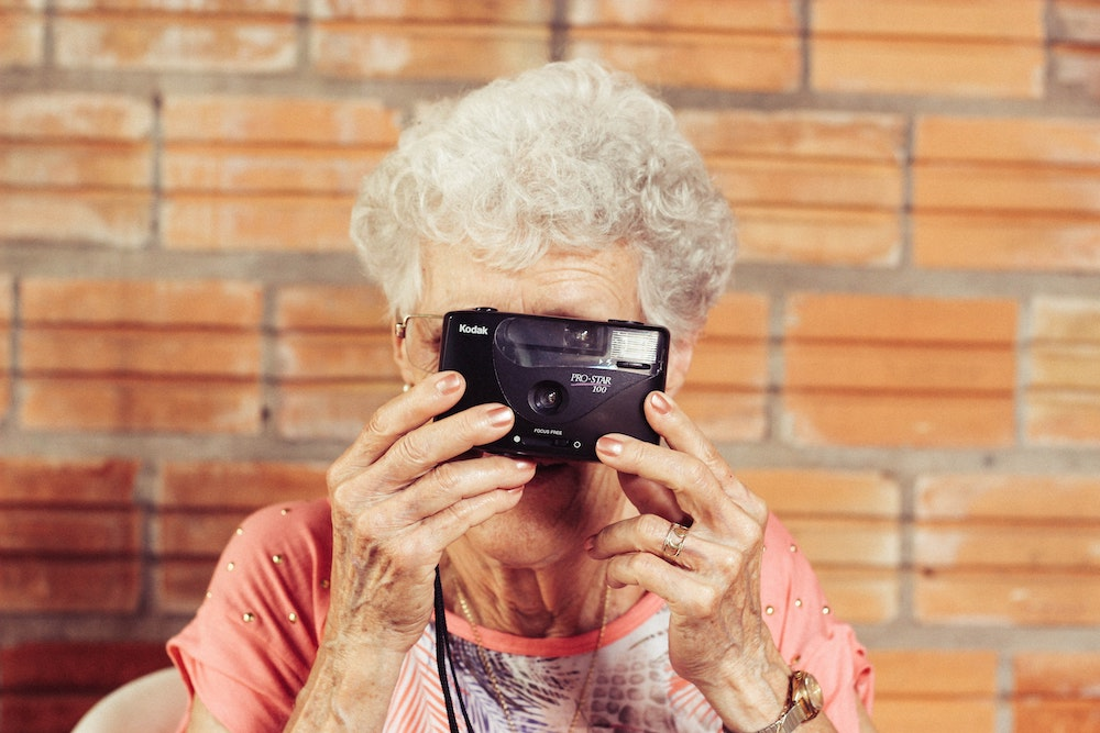 older lady taking photo with a camera