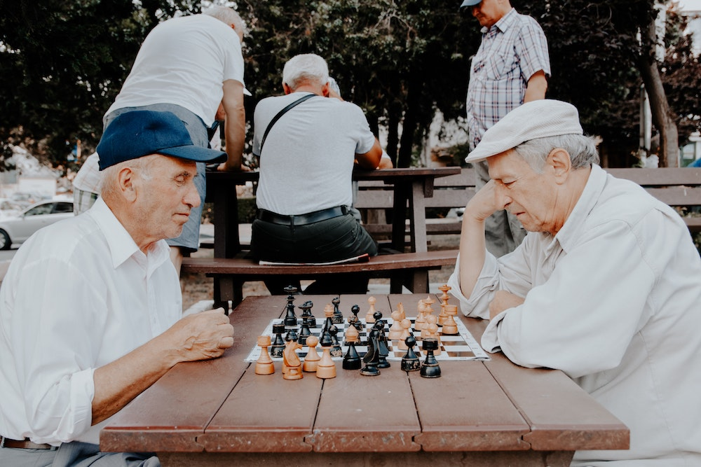 two older men playing chess outside
