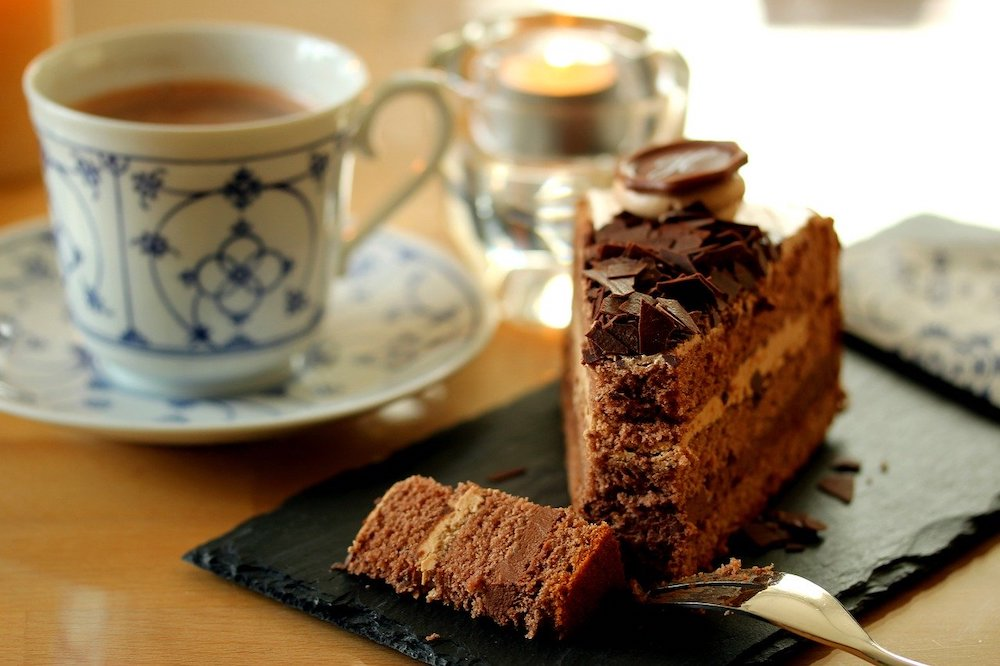 A cup of tea and slice of chocolate cake.