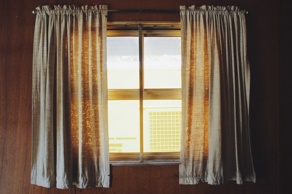 A window with cream curtains.